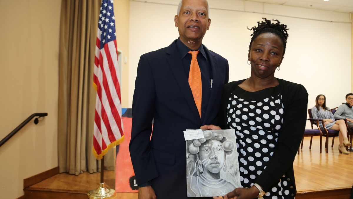 "Rep. Johnson stands with grand prize winner Arantza Pena Popo's mother Maria Popo and the winning piece ""Cultural Portrait"" during the reception. Arantza was attending a college preparatory class and could not attend the Saturday event."